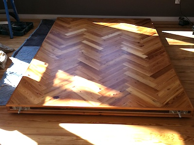 <p>Sliding Parlor Door. This door was constructed using re-claimed long leaf pine laid up on a steel core door in a herringbone pattern. Yes, it is a heavy door, but slides with ease on a hidden track recessed into the ceiling.</p>